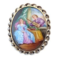 A 19th Century silver gilt brooch set with hand painted ceramic cabochon
