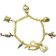 Charm Bracelet With Authentic Tierracast Real 22K Gold Plated Charms And Heart Shape Clasp Made in USA
