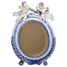 Porcelain Mirror with Cherubs, Gilded Accents, and a Floral Motif