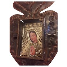 Vintage niche depicting Mother Mary..  She is protected behind a hinged glass door..