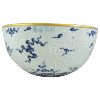 Chinese Blue and White Ceramic Bowl with Molded Dragons and a Central Flower