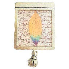 HALLMARK signed Leaf with Writing Framed in Pewter Brooch with Ladybug Charm