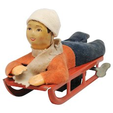 Vintage Wind Up Boy on Sled or Toboggan Japan