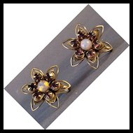 White metal stylized flower earrings with opalescent and purple stones