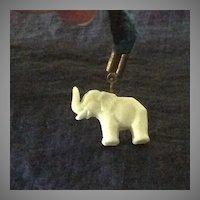 Celluloid elephant on a wool strand