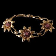 Signed Simmons gold tone flower bracelet with amethyst colored center stones
