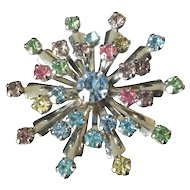Starburst multi-colored rhinestone brooch set in white metal
