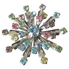 Starburst multi-colored rhinestone brooch set in white metal