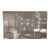 Real Photo postcard featuring a man in his dry goods store
