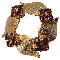Gold Tone Circle pin with leaf motif and amber prong-set rhinestones