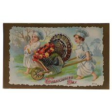 Thanksgiving postcard with Turkey in a Wheelbarrow Pushed by Two Little Chefs.