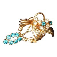 Vintage gold tone pin with clear and turquoise rhinestones