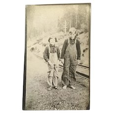 Unused Real Photo Post Card Barefoot Boy and Girl in Overalls by Railroad Tracks.