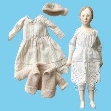 Wooden art doll in a white polka dot dress