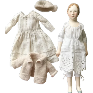 Wooden art doll in a white polka dot dress