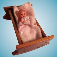 Wooden Cradle with an ES Baby Doll in a Pink Blanket