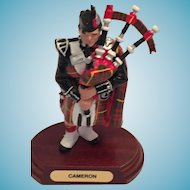 Scottish Piper in red, green, and yellow 'Cameron' Tartan Regalia