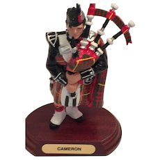 Scottish Piper in red, green, and yellow 'Cameron' Tartan Regalia