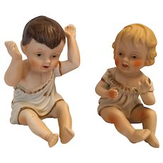 Circa 1950s Sitting Girl and Boy Bisque Piano Babies by Norleans Japan