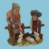 1960s-70s Porcelain Figurine of a Lady and Boy Feeding Bunnies.