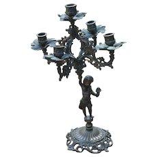 Candelabra with ornate bronze cherub holding center piece main candle array