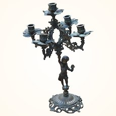 Candelabra with ornate bronze cherub holding center piece main candle array