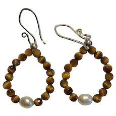 Faceted Tiger eye stone beads circle a lone cultured Pearl