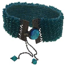 Teal crystal bracelet embellished with bronze scrolled edges closes with dichroic button