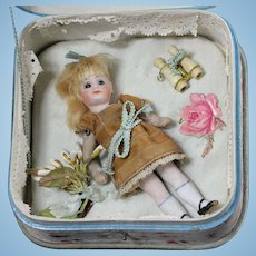 "Antique French All - bisque 4.3"" mignonette doll in a wonderful silk presentation box  with roses, circa 1890's"