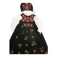Black sleeveless embroided dress with white long sleeve chemise featuring a matching bonnet