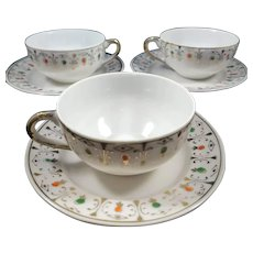 Delicate thin porcelain tea cups and saucers, gold trim with green and gold.  Set of three(3).   Tea cups 2.75 inches diameter, saucers 4.125 inches in diameter.