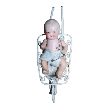 Painted Bisque Japanese made miniature doll in metal wheelbarrow