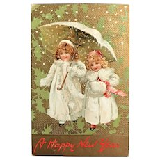 """1909 TUCK'S """"New Year"""" Series Postcard - Two Little Girls in White Coats and Umbrella"""