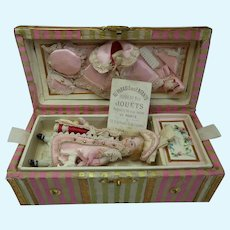 Endearing small all bisque doll in an antique trunk and her trousseau!