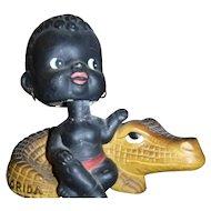 Nodder Black Boy sitting on Aligator