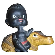 Nodder Black Boy sitting on Aligator