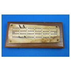 Fossilized Bone cribbage board on wooden base