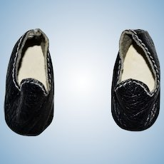 Pair of tiny black leather shoes with White Stitching