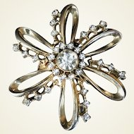 Round gold-tone brooch with six petals and large Rhinestone center