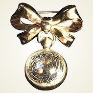 Golden-tone bow with lucite sphere containing a mustard seed brooch by Coro