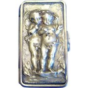 Twin cherubs motif match safe, brass with alligator skin trim, c. 1890
