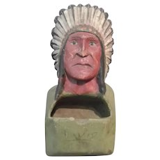 A Carved Match Holder in the Form of a Native Chief in Head Dress