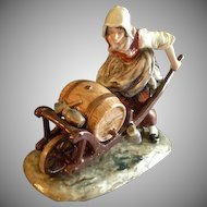 "Ernst Bohne Sohne/Volkstedt Germany Porcelain Figurine ""Woman with Wheelbarrow Holding a Whiskey Keg"""