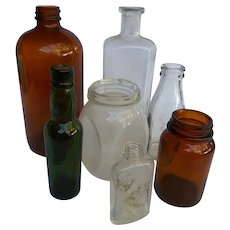 Vintage group of 7 glass bottles for flowers or as rustic decor