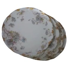 """Set of 4 Haviland Limoges 8 1/2"""" plates with blue and pink floral sprays and gold gilded edge, circa 1900, imported by Weichel and Millar."""