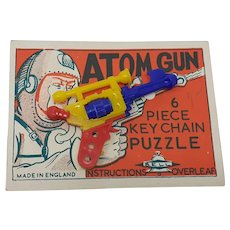 Bell Plastic keychain Puzzle Atom Gun Carded