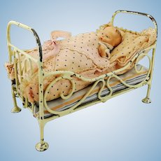 Antique dollhouse bed, 6 by 3 inches with baby doll and bedding