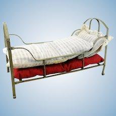 "Antique metal doll crib, original bedding, 1910s made, 12"" long"