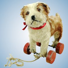Steiff Molly dog puppy with ff button, red label, on eccentric wheels, 1927 to 42