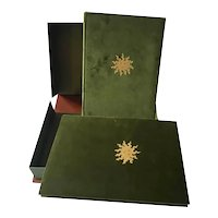 Two velvet books cased in a brown leather book cover.